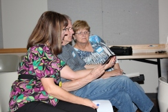 Terri with friends viewing the captioning tablet